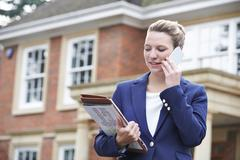 Female Realtor On Phone Outside Residential Property - stock photo
