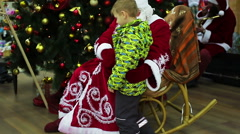 Cheerful kid sitting on Santa Claus knees to make Xmas wish, happy childhood Stock Footage
