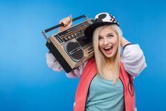 Woman holding retro boom box - stock photo