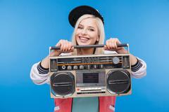 Smiling woman holding boom box - stock photo