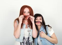 Two young girlfriends indulge and grimace, make each other a mustache out of the - stock photo