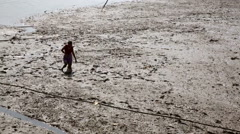 Asian woman in river mud gathering bate Stock Footage