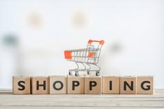 Shopping cart on a wooden sign - stock photo