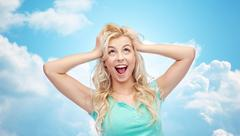 Smiling young woman holding to her head or hair Stock Photos