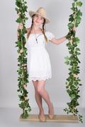 full-length Beautiful young leggy blonde in a little white dress and white - stock photo