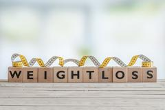 Weightloss sign with measure tape - stock photo
