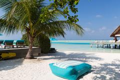 parasol and sunbeds by sea on maldives beach - stock photo