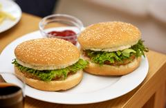 close up of two hamburgers on table - stock photo