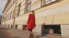 Young blond woman walking in European city on Sunny spring day - stock footage