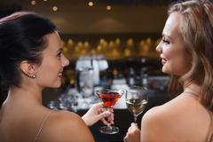 Happy women with drinks at night club bar Stock Photos