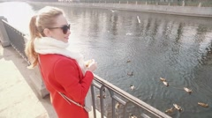 Young blond woman feed ducks in on a sunny spring day Stock Footage