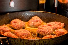 Raw meatballs on a frying pan - stock photo