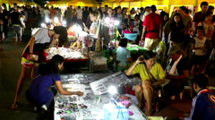 Asian night market Woman selecting from lit bracelet display with smiling vendor Stock Footage