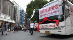 Blood donation bus in a popular shopping street in Shanghai, China - stock footage