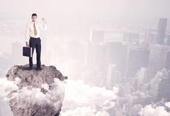 Stock Photo of Winner business person standing on rock