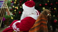 Happy Santa Claus waving hand in rocker chair to welcome shopping mall visitors Footage