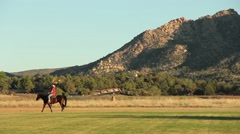 Woman Rides Horse Past Mtn Stock Footage