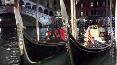 Venetian gondolas tied near Rialto bridge, Venice, Italy, panning shot Stock Footage
