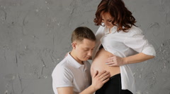 Happy young man nuzzles the belly of his pregnant wife. Young wife pats him on Stock Footage