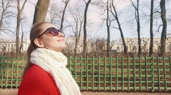 Young blond woman walking in European Park and smiles on Sunny spring day - stock footage