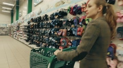 Young blond woman chooses clothes in supermarket - stock footage