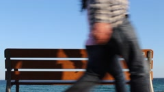 Stock Video Footage of Wooden Bench at the ocean. People passing by walking.