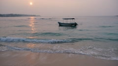 Calm sea with a alone sway boat at sunrise, Sri lanka, Unawatuna beach - stock footage