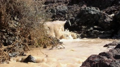 Brown mud water running over and between stones Stock Footage