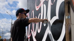 Young graffiti artist working in the street Stock Footage