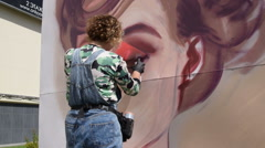 Female graffiti artist drawing a portrait Stock Footage