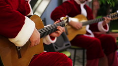 Male guitarists in Santa suits playing joyful songs at Christmas eve concert - stock footage