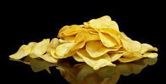 Many potato chips on black background - stock photo