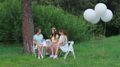 Beautiful girls, picnic outdoors in the park. White balloons and a table with sw - stock footage