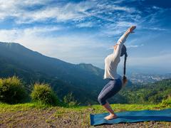 Woman doing yoga asana Utkatasana outdoors - stock photo