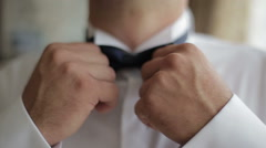 Groom puts on his bow tie . Close-up. - stock footage
