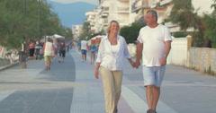 Couple having enjoyable walk on summer resort Stock Footage