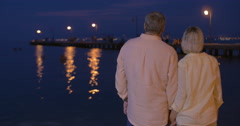 Loving senior couple on water-front at night - stock footage