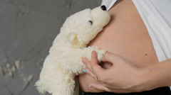 Happy pregnant woman on a gray background. Keeps Teddy bears in his belly. Slow Stock Footage