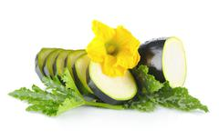 Mature courgette cut into slices with flower and courgette leaves on white ba - stock photo