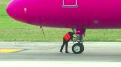 Pilot inspecting landing gear of Boeing 737-528 aircraft before takeoff Stock Footage