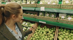 Young blond woman sniffs the pear in supermarket - stock footage