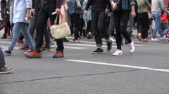Shoes and legs of pedestrians crossing a busy zebra in Shanghai, China Stock Footage
