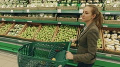 Young blond woman walk along shelves with fruits in supermarket - stock footage