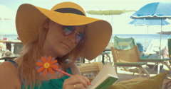 Close-up of young blonde woman writing in notebook Stock Footage