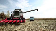 Combine harvester prepared to unload corn grains in truck - stock footage