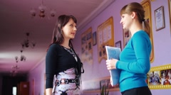 Two teachers in a school talking to each others Stock Footage
