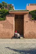 Photo of an old man asleep in a doorway of a house in Marrakesh Morocco - stock illustration