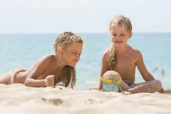 Two little girls are playing with enthusiasm in the sand on the seashore Stock Photos