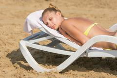 Young tanned woman lying on a deck chair with his eyes closed on the beach Stock Photos