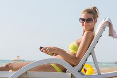 Girl on a deck chair on the beach with a smile look in the frame Stock Photos